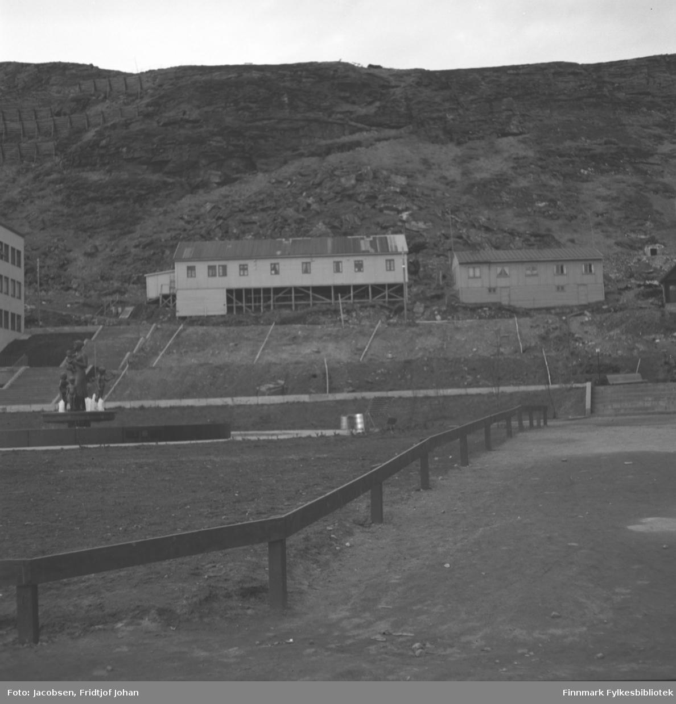 Rådhusplassen, fontenen på Ole Olesens plass til venstre i bildet. Bygningen som såvidt syns til venstre på bildet er DNB-bygget. Starten på sikksakkveien ligger like bak. Lengst til venstre i den lange brakka midt på bildet begynte Ernst Larsson sin sportsforretning i 1948. Dette var en av de siste brakkene som ble revet i Hammerfest, og den hadde nummer 276. I den høyre delen av brakka drev B. Hansen forretning. Fjellet i bakgrunnen er Salen og noen skredvern ses i fjellsiden.