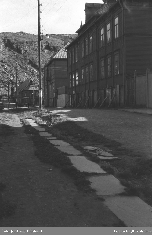 Bildet tatt nederst i Storgata og opp mot Salen. Storgata er en ganske bred grusvei. Steinheller ligger ved siden av veien og litt gress vokser rundt dem. En lav grøft går mellom veien og steinhellene, muligens en dreneringsgrøft. Bygget til høyre er Middelskolen. Bygget er mørkmalt, har liggende panel og mange avlange vinduer. Det har to arker og skiferdekke på taket. Stokker står som støtte på veggen nederst. Bortenfor det ligger bygget til Sorenskriveren og politiet. Det er også ganske mørkmalt med liggende panel og mange vinduer på langsiden. Det har et bratt tak med skiferdekke på. Flere bygninger ligger langs gata opp mot fjellet Salen. Det tredje på høyre side ligger i krysset med Sørøygata. Det har mange vinduer, skiferdekke på det valmede taket og et skilt på veggen. I kjelleren/1. etg ligger Suppekjelleren. På venstre siden står lykte- og el-stolper langs gata. Et parkeringsskilt ses på venstre side. Sola skinner og det ser ganske så sommerlig ut.