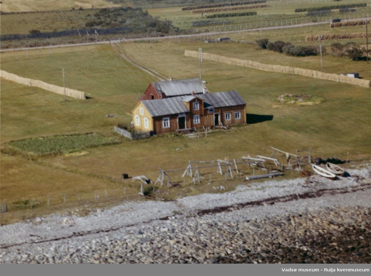 Flyfoto av Paddeby, Vadsø kommune, 1963. Gård, fiskehjell og båter. Øverst til høyre jordene til Niska.