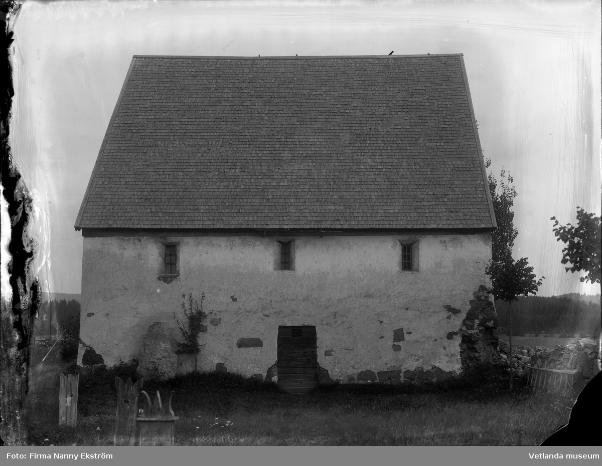 Tiondeladan i Alseda intill kyrkan. I förgrunden syns gravstenar av trä och lutad mot byggnaden är en runsten.