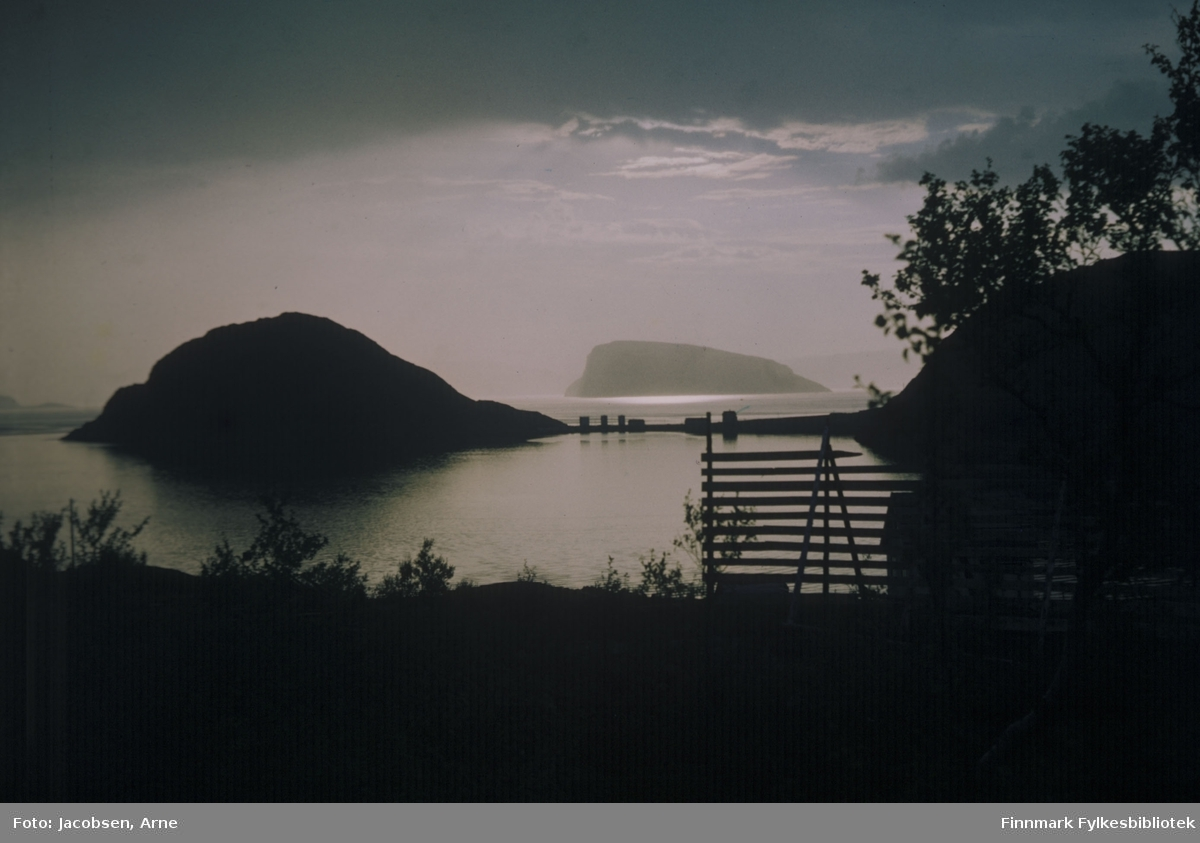 Rypklubben, til venstre på bildet, fotografert en sommerkveld/natt. Et mørkt skylag dekker deler av himmelen, men øya Håja ligger i Sørøysundet, badet i sol. Midt på bildet er Rypklubbeidet med Shells tankanlegg og Rypefjell til høyre. Bildet er tatt fra Bjørkåsen og som man ser har trærne godt med løv. Havområdet nærmest er Rypefjorden, som på bildet ligger blikkstille. Et hus kan såvidt ses nede til høyre og en gjell står midt på bildet.