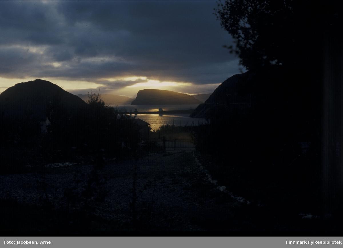 Solstråler over Håja. Ellers er det mørke, tunge skyer. Et lite glimt av Rypefjorden og Sørøysundet med Rypklubbeidet som skille. Huset og tankanlegget ses mot sjøen og Rypefjell til høyre. Noe diffust ses Sørøya bak Håja. Siluetten av et hus ses mot Rypefjorden. Noen trær med mye løv og deler av et gjerde ses. Ellers ser man bare omriss av et mørkt område siden bildet er tatt en sommer/tidlig høst-kveld fra Bjørkåsen i Rypefjord.