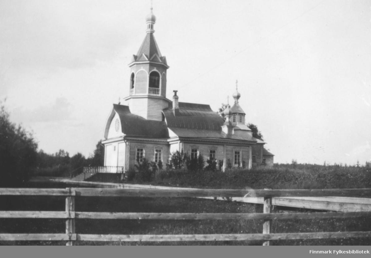 Bilde av Tempelkirken som ligger i Petsamo i Russland. Bygningen er i tre. Den har tårn med kupler og spir. Området rundt kirken er frodig med busker og trær. I forgrunnen på bildet er det et tregjerde