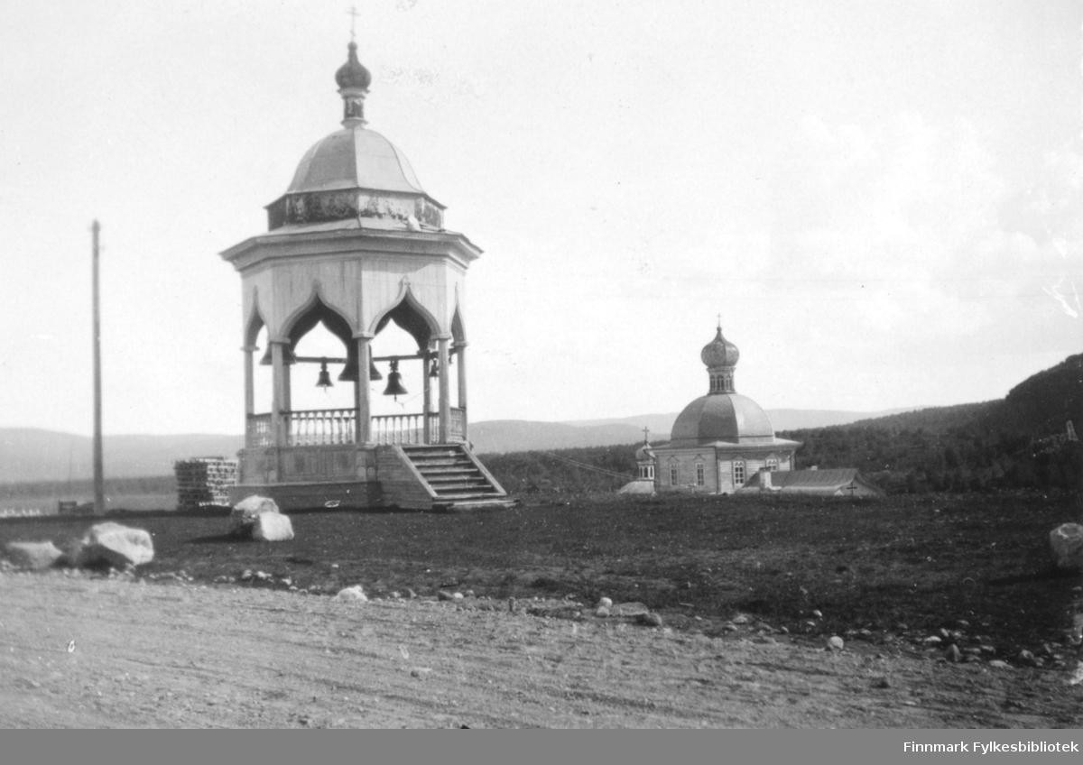 Bilde av en trepaviljong med kuppel og spir i Petsjenga Nedrekloster. Det henger flere klokker inni. Bakenfor er det en annen trebygning, en kirke eller et kloster. Den har også kupler og spir på taket. På fotografiet kan man se fjell i bakgrunnen. Det står en høy stolpe til venstre på bildet