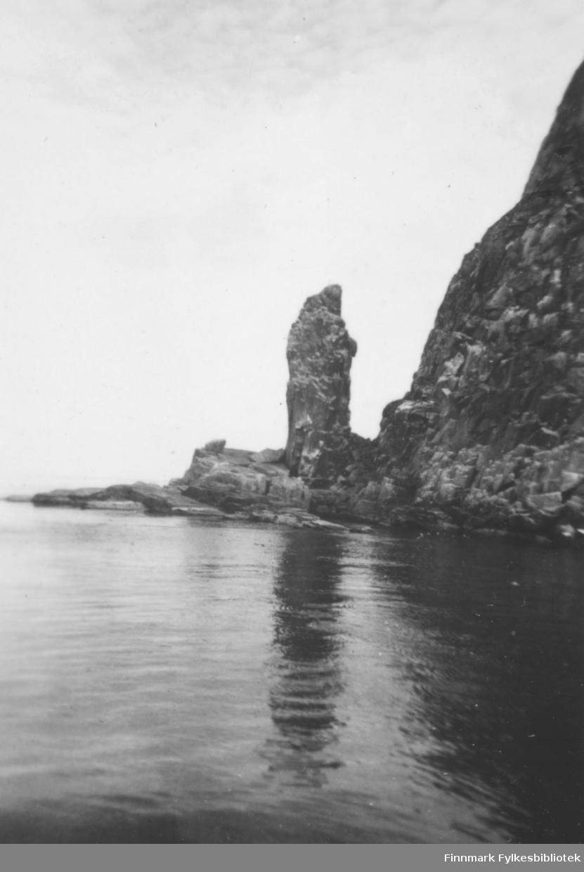 Fotografi av en steinklippe som står nede ved havet. Til høyre er det fjell
