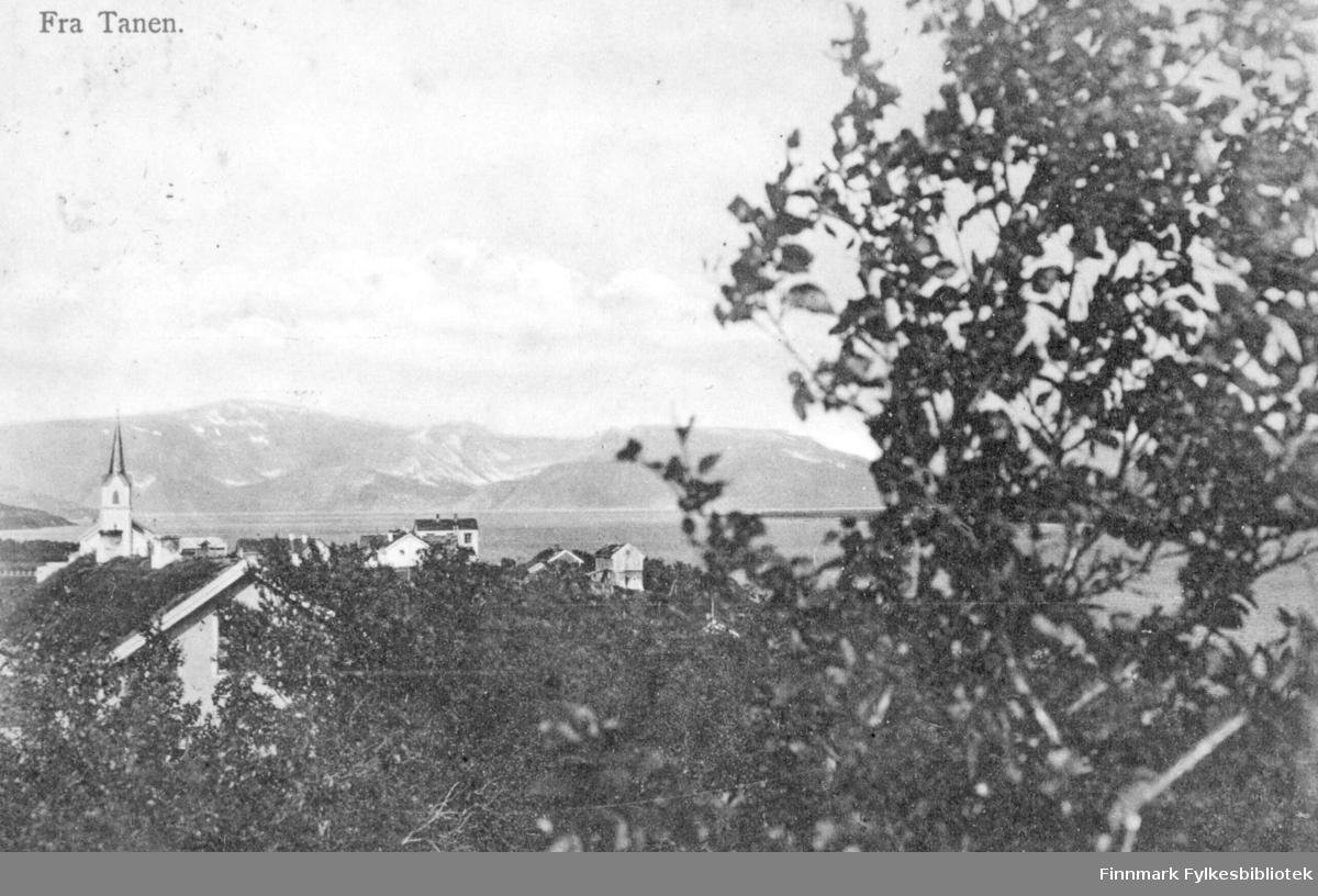 Postkort fra Tanen. På fotografiet ser vi noen bygninger omkranset av trær. Det ligger en kirke til venstre i bildet. På andre siden av vannet er det fjell