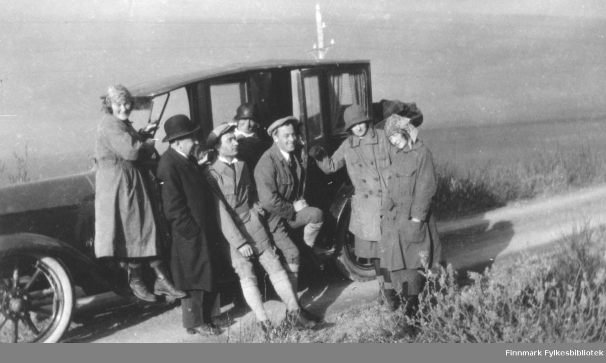 Fotografi av fire kvinner og tre menn som står ved en bil som nok er fra 1910 eller 20-tallet. De er alle kledt i fritidsklær utenom en mann som er kledt i en mørk frakk og hatt. Bilen står på en grusvei