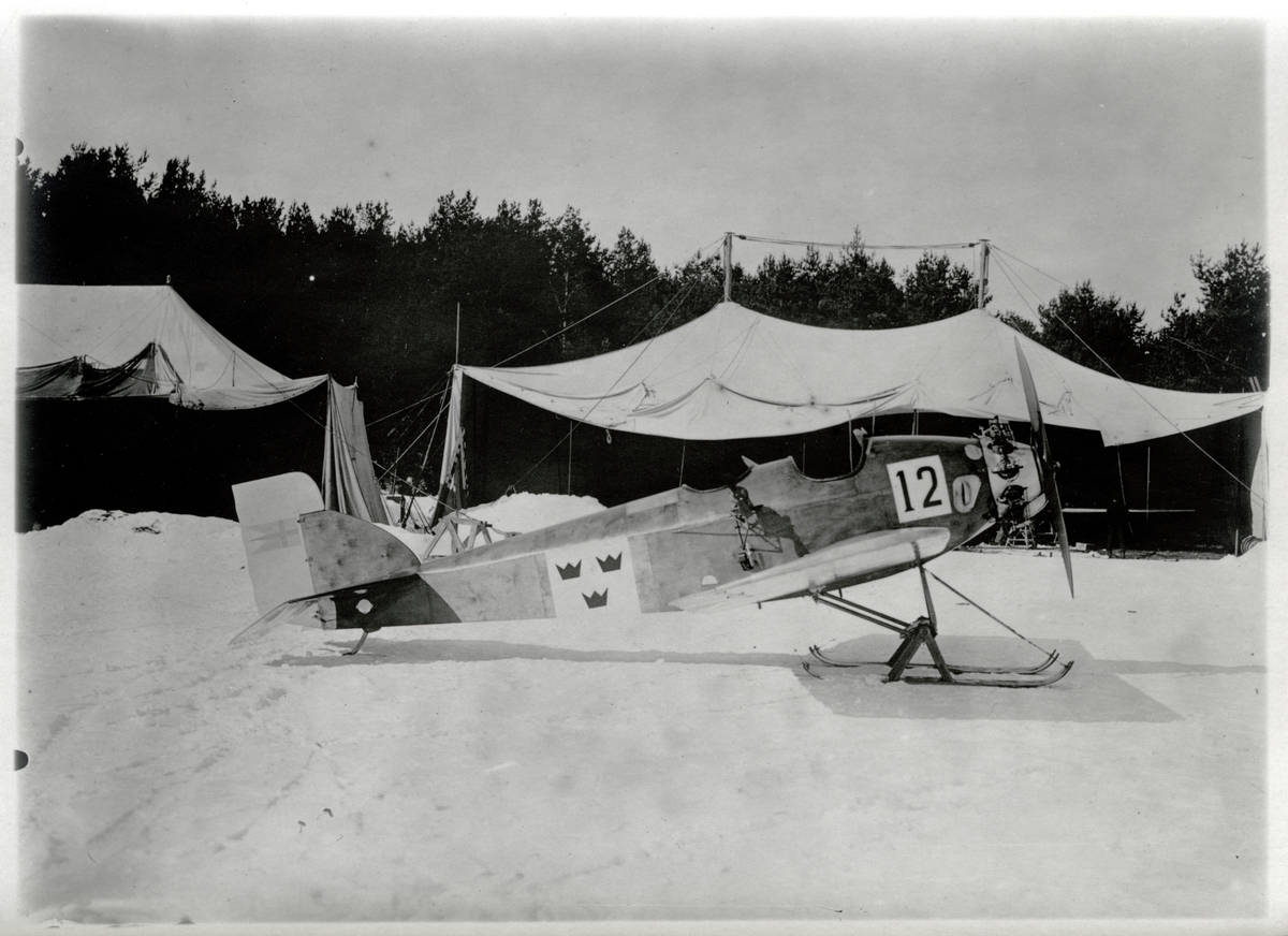 Övrigt: Heinkel HE 3 anskaffades 1923 i två exemplar (nr 11 och 12) till Marinens Flygväsende. De användes fram till 1927 som skolflygplan vid Hägernäs, och flygplanstypen kom att kallas för Paddan. Motor Siemens Sh6 100 hkr, spännvidd 12,10 m, längd 7,20 m. Flygplan nummer 12, som ses på denna bild, överfördes 1927 till Flygvapnet men såldes kort därefter till en privatperson som SE-AABI. Det ströks ur civilregistret efter ett haveri i januari 1929 då flygföraren omkom.