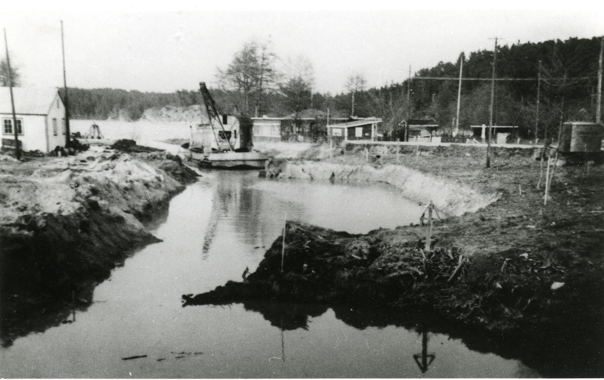 Gamla Dalarö. Kanalbygget. Sista etappen av kanalbygget, som stod klart i maj 1939. Kanalen och hamnbygget vid Askfatet hade kostat 197.000 kr av vilken staten betalade 90%. Det gamla bussgaraget till vänster finns fortfarande kvar. T.h. dansbanan, som revs i slutet av 1940-talet.