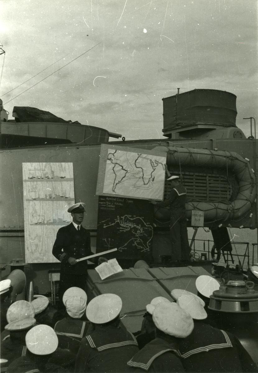 En kapten undervisar i stridstaktik. Orienteringen sker på däck inför en grupp soldater.