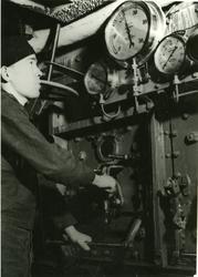 Besättningsman kontrollerar tryckmätare i maskinrummet.