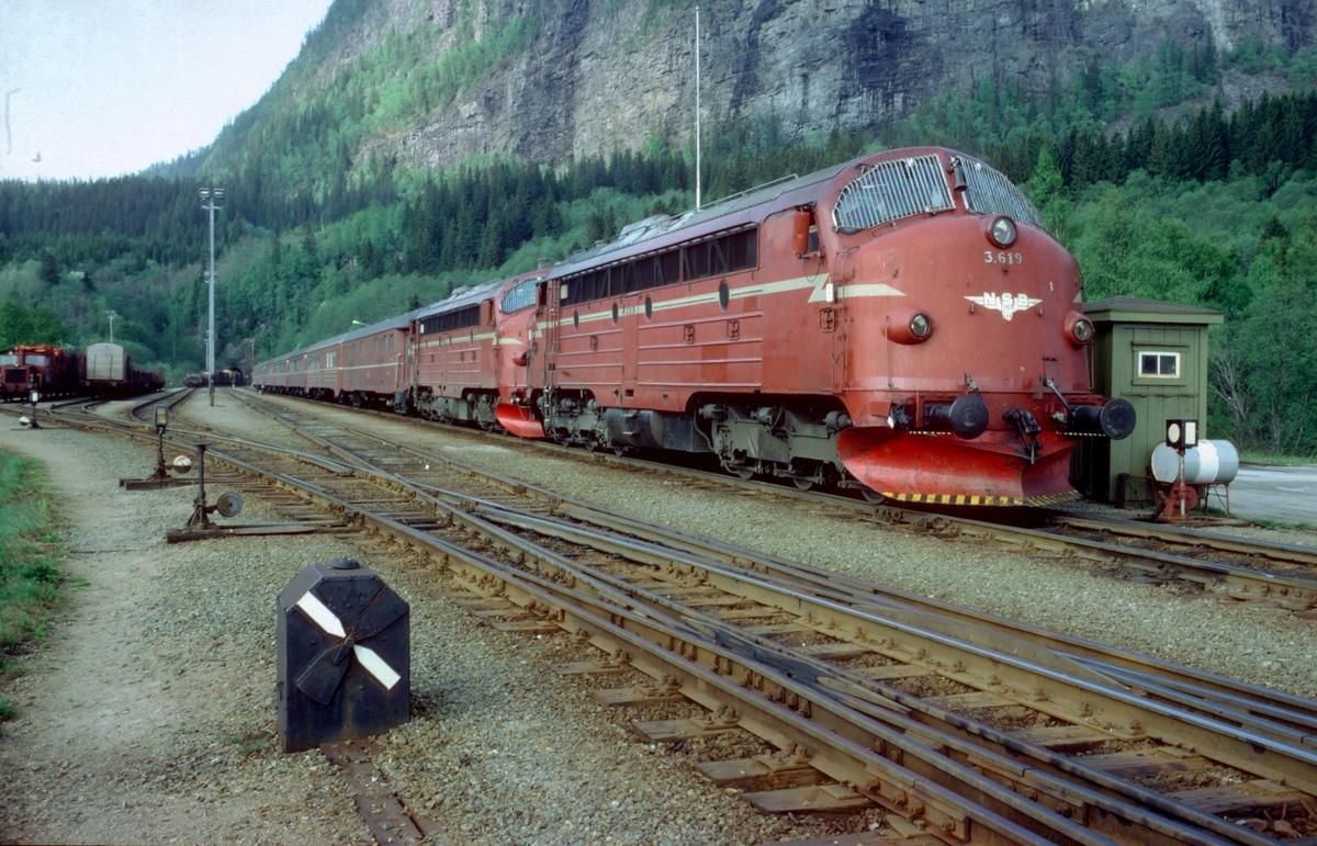 Dagtoget fra Bodø til Trondheim, hurtigtog 452, på Grong stasjon med to dieselelektriske lokomotiver NSB type Di 3 og vogner type 3. I forgrunnen mekanisk kryssporvekselsignal. I bakgrunnen sees slutten på nordgående godstog som er på vei inn i tunnelen.
