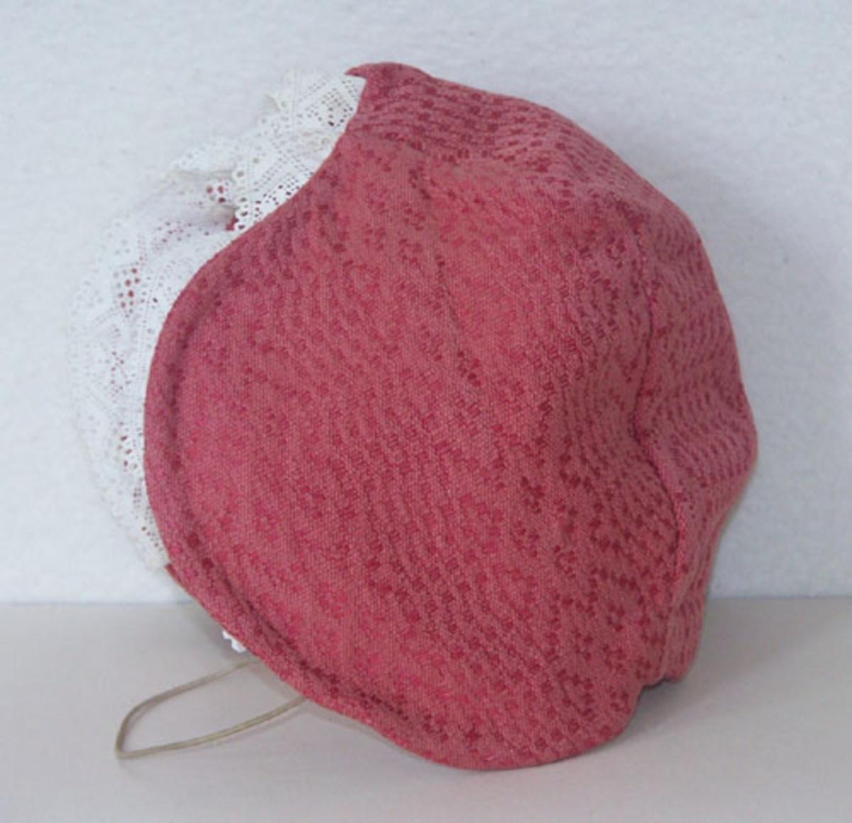 Mjuk mössa till Sunnerbodräkten sydd i rosa daldrällstyg, samma tyg har använts till Sunnerbodräktens livstycken.Mössan kantas fram av en vit spets.På insidan finns en snodd fastsydd och en etikett från Kronobergs hemslöjd Växjö.