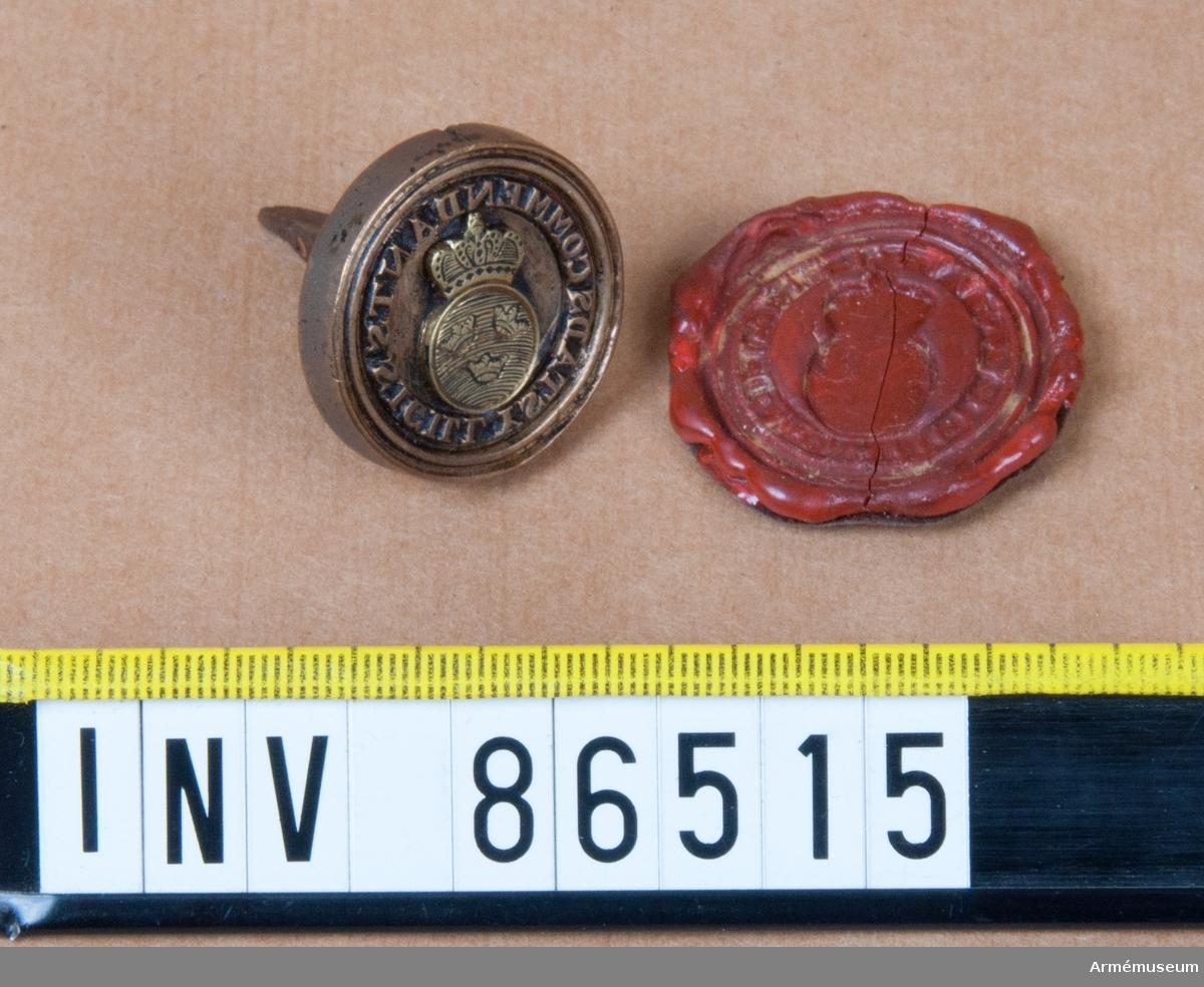 Grupp M V. Innanför texten en krönt, räfflad, rund sköld med Sveriges tre kronor, ställda så att den nedersta står upprätt och de två översta luta utåt var sitt håll, allt omgivet av två släta ränder. Med avtryck i röd lack.
