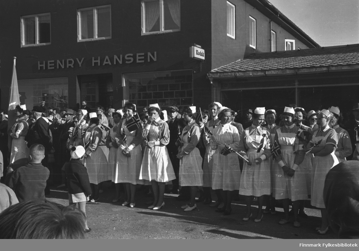 En gruppe sykepleiere i uniformer, samt noen andre mennesker står ved Henry Hansens fotoforretning og feirer med flagg i hendene. Dagen er solrik og det er sommer.