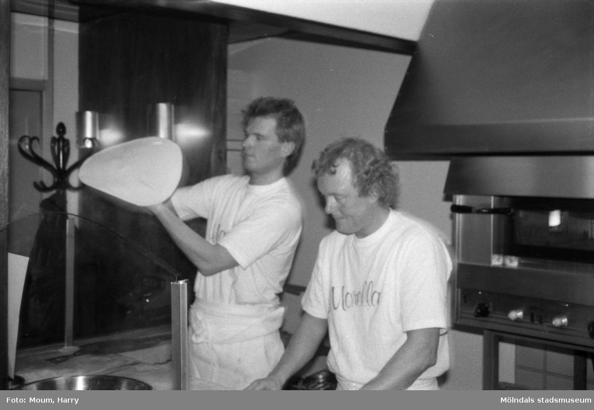 """Nya restaurangen """"Morella"""" i Lindome centrum, år 1985. """"Håkan Lundell kan det där med att schwunga till en pizza. Vid arbetsbänken ses Rustan Pettersson.""""  För mer information om bilden se under tilläggsinformation."""
