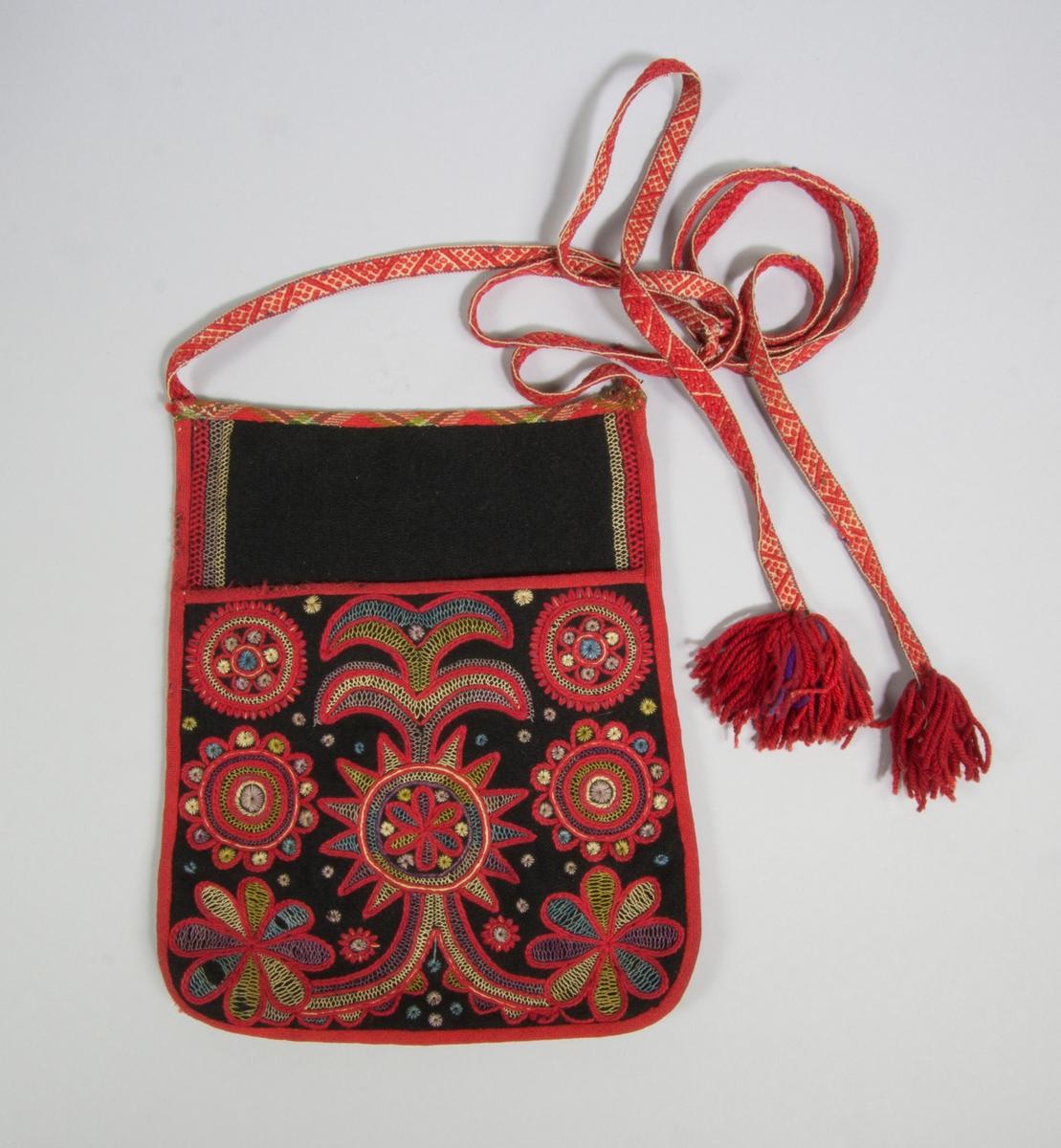 Kjolsäck till dräkt för kvinna från Bjursås socken, Dalarna. Modell med avskuret framstycke. Tillverkad av svart ylletyg, vadmal, med broderi av rött ullgarn och silkegarn i flera färger: stjälksöm, flätsöm, sticksöm. Motiv: med stjälksöm sydd centralt placerad blomma med uppstigande parvisa blad och nedtill slingor med blommor, på sidorna parvis två olika blommor, utfyllnadssömmar av flätsöm och sticksöm. Överstycket av svart vadmal med kantbroderi av flätsöm. Framstycket fodrat med linnetyg i tuskaft, eventuellt sekundärt. Kantat med rött diagonalvävt ylleband, utom överkanten som har ett rutigt diagonalvät band. Bakstycke av handvävt linnetyg, kypert. Knytband handvävda, med plockat mönster av rött ullgarn på vit botten, i var ände en tofs av rött ullgarn med lite lila garn.