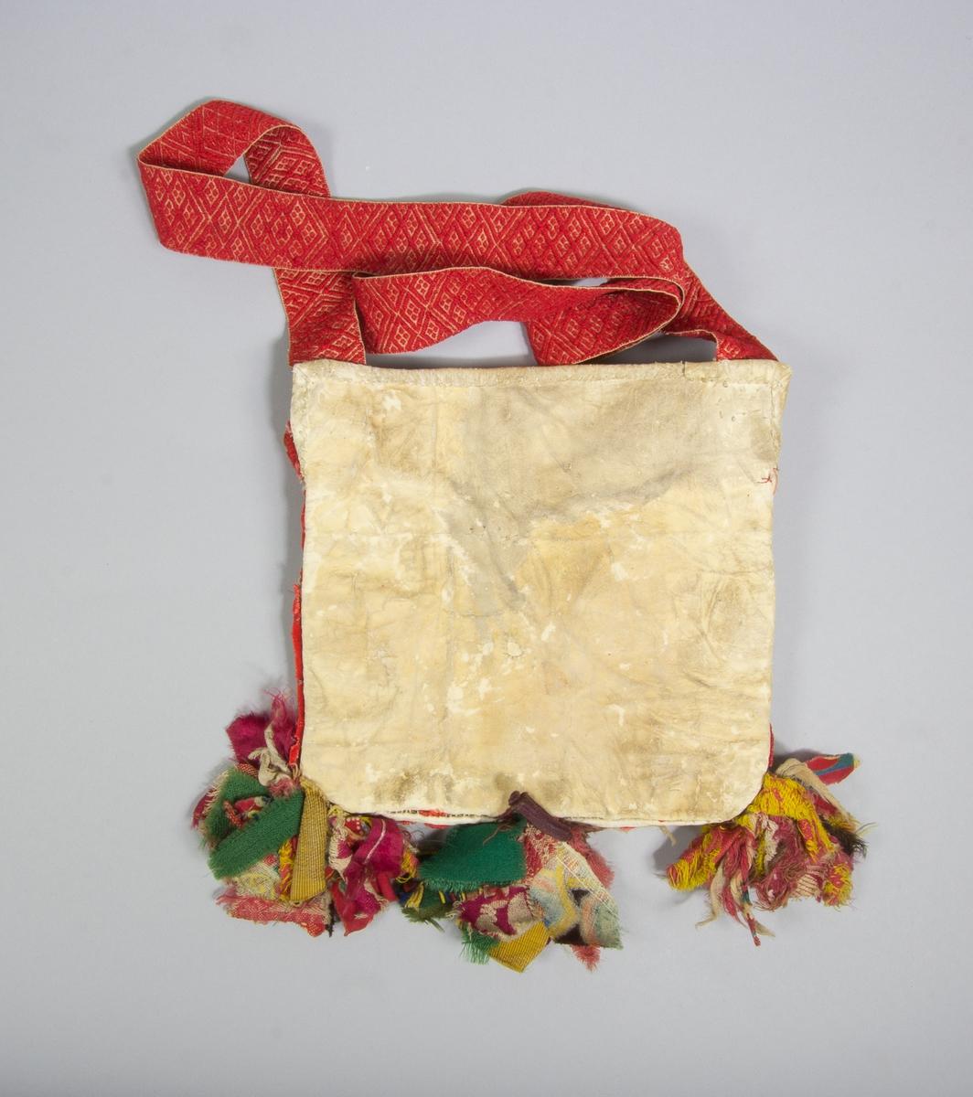 """Kjolsäck till dräkt för kvinna från Rättviks socken, Dalarna. Modell med avskuret framstycke. Tillverkad av vitt fårskinn, med applikationer av ylletyg, kläde, i rött, grönt och gult, fastsydda med lingarn, efterstygn. Centralt placerad stor hjärtblomma med omgivande mindre blommor i hörnen och andra figurer. Broderi utfört med silkegarn i många färger: flätsöm, plattsöm, sticksöm. Märkt med klippta tecken: BJ 1868. Extra dekoration av sju vita porslinsknappar. Ovanför applikaionen en remsa rött kläde med flätsöm, ovanför den en """"grind"""" flätad av smala remsor rött och grönt kläde samt vitt skinn. Framstycket fodrat med vitt fabriksvävt bomullstyg, tuskaft. En remsa rött kläde inlagd i sido- och bottensöm. I nederkanten fäst tre tofsar av olika tyger. Överstycke av bomullstyg, tryckt mönster i flera färger på röd botten, kattun. Bakstycke av vitt, rakat fårskinn. Axelband handvävt, med plockat mönster av rött ullgarn på vit botten. Vid bandets fäste sitter tre bollar av ullgarn."""