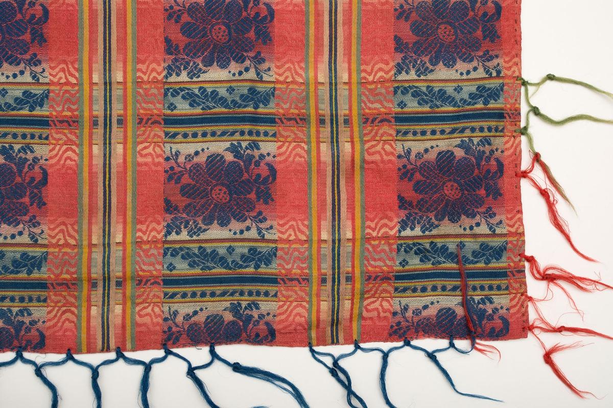 """Mönstervävd schal med frans. Schalen är rutig med både enfärgade och mönstrade ränder. En ruta, 65 x 70 mm, är mönstrad med en blå blomma och blad på en botten som skiftar i rött till gult. Blommotivet upprepas sju (hela) gånger på bredden och sex gånger på längden. Iknuten frans längs sidorna i rött, blått och grönt. Fransen är ca 90 mm lång, mycket sliten, ca 25-30 mm mellan varje knut. Stadkant i två sidor, smal fåll i två sidor.  Varp och inslag troligen helt och hållet i kulört lingarn.Frans i ullgarn. Märkt med en påsydd tyglapp med texten: """"N° 204 b."""". Mått exklusive frans."""