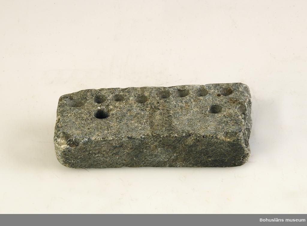 Ur handskrivna katalogen 1957-1958: Gjutform, sten för knappar Mått: 10 x 4,2 x 1,2 cm; Täljsten; en del av formen avbruten.  Lappkatalog: 33