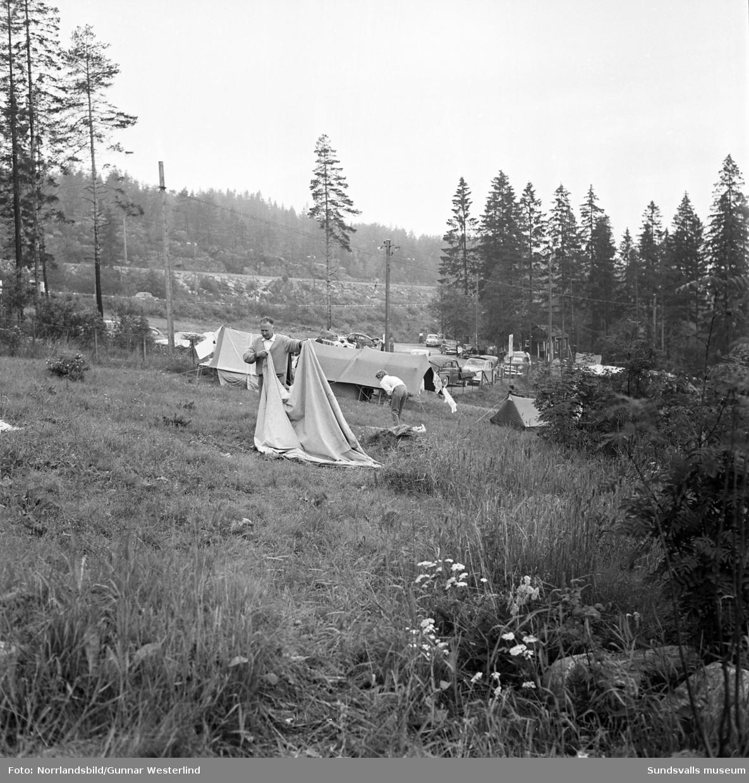 En serie bilder från Fläsians camping och badplats. Bland annat en Malmöfamilj som packar sin Vauxhall för avfärd. Tältet surras på taket av tonårssönerna och packningen stuvas i skuffen av mor i familjen. Lillebror agerar glad kartläsare medan far står i bakgrunden och ser en aning utpumpad ut.