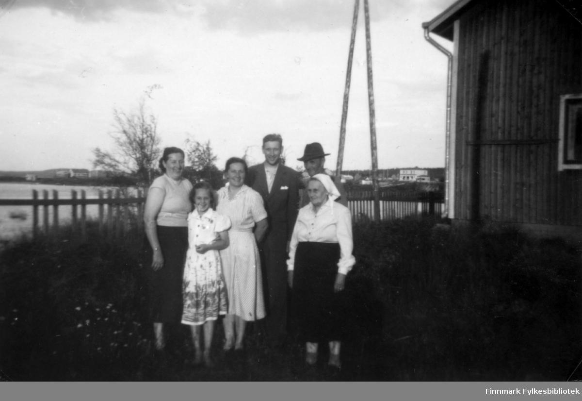 Fotografi av tre kvinner, to menn og ei jente. Fra venstre står Henrika Sotkajærvi, Jenny Ranta med datteren Orvakki, Abraham Ranta, Olav Ranta og Hilma Ranta med skaut på hodet. De står utenfor et trehus. I bakgrunnen ses hus og bygninger på den andre siden av sjøen. Et gjerde går langs sjøsiden
