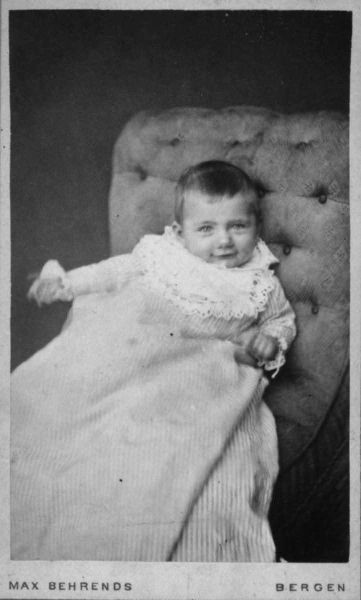 Portrett av et blidt barn i lang kjole - det er vanskelig å si om dette er ei jente eller en gutt. Barnet ser ut til å være 1-2 år