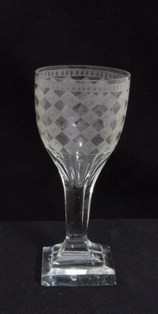 Vinglas av glas vars kuppa dekorerad med etsat harlequinmönster och stjärnor. Slipat ben, kvadratisk slipad fot.