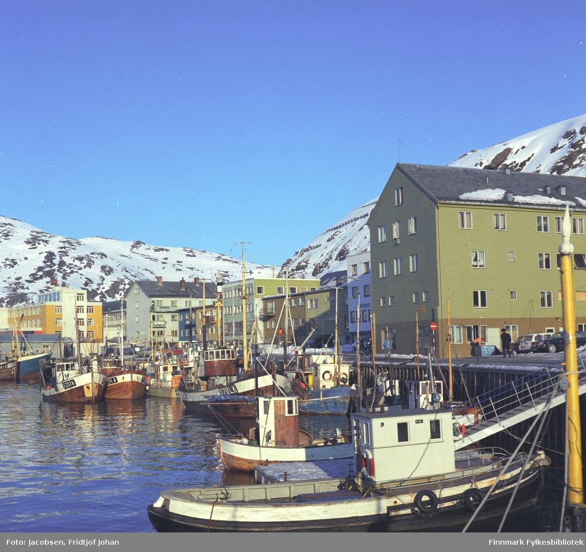 """Hammerfests indre havn sett fra Rådhuskaia. Båten nærmest kamera er havnevesenets """"Havna 1"""". Det store bygget til høyre på bildet er Samvirkelaget. Findusanlegget ses helt til venstre på bildet med Mollafjell i bakgrunnen."""