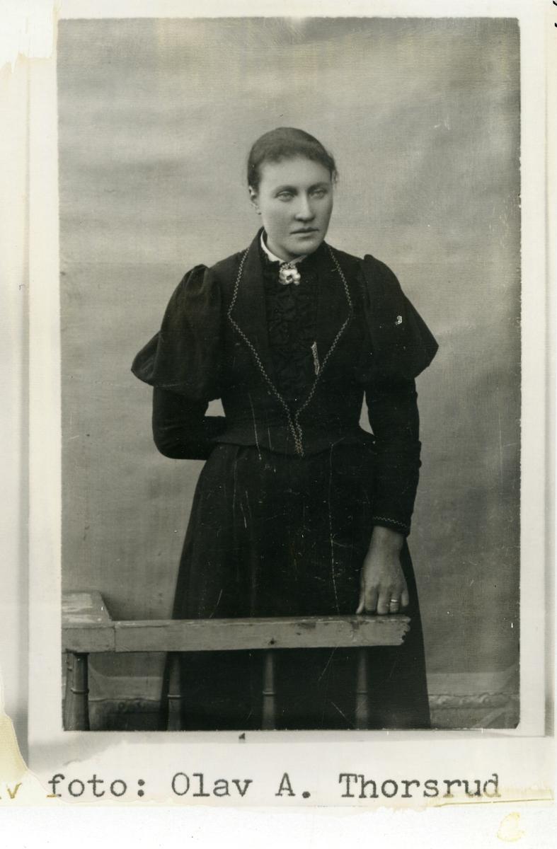 Portrett av ukjent kvinne. Står foran lerret. Svart kjole, sølje i halsen.