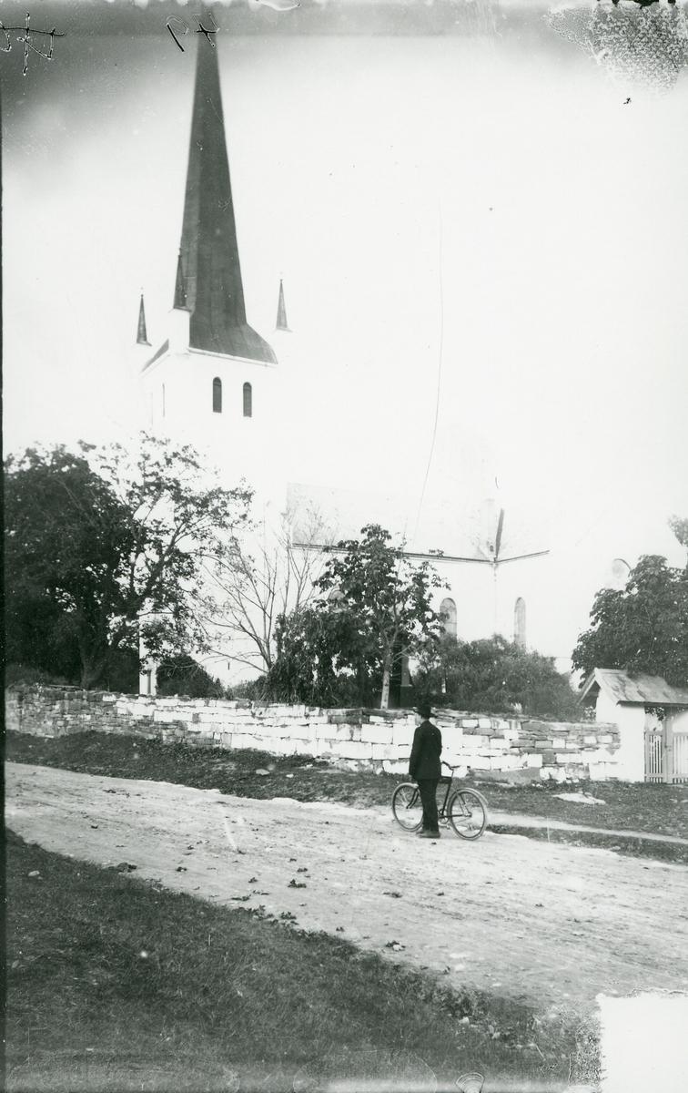 Norderhov kirke. Mann med sykkel oppstilt foran steinmuren som omgir kirka.