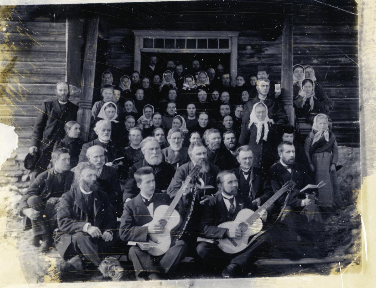 Vekkelsesmøte. Kvinner og menn oppstilt i gruppe foran bygningen på Bangsødegård, Sør-Aurdal. To av mennen foran har gitarer.