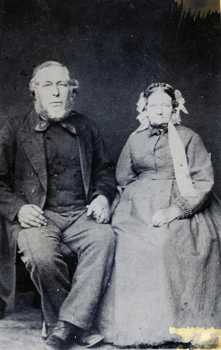 Kvinne og mann sittende foran lerret. Foto tatt i slutten av 1860-åra.