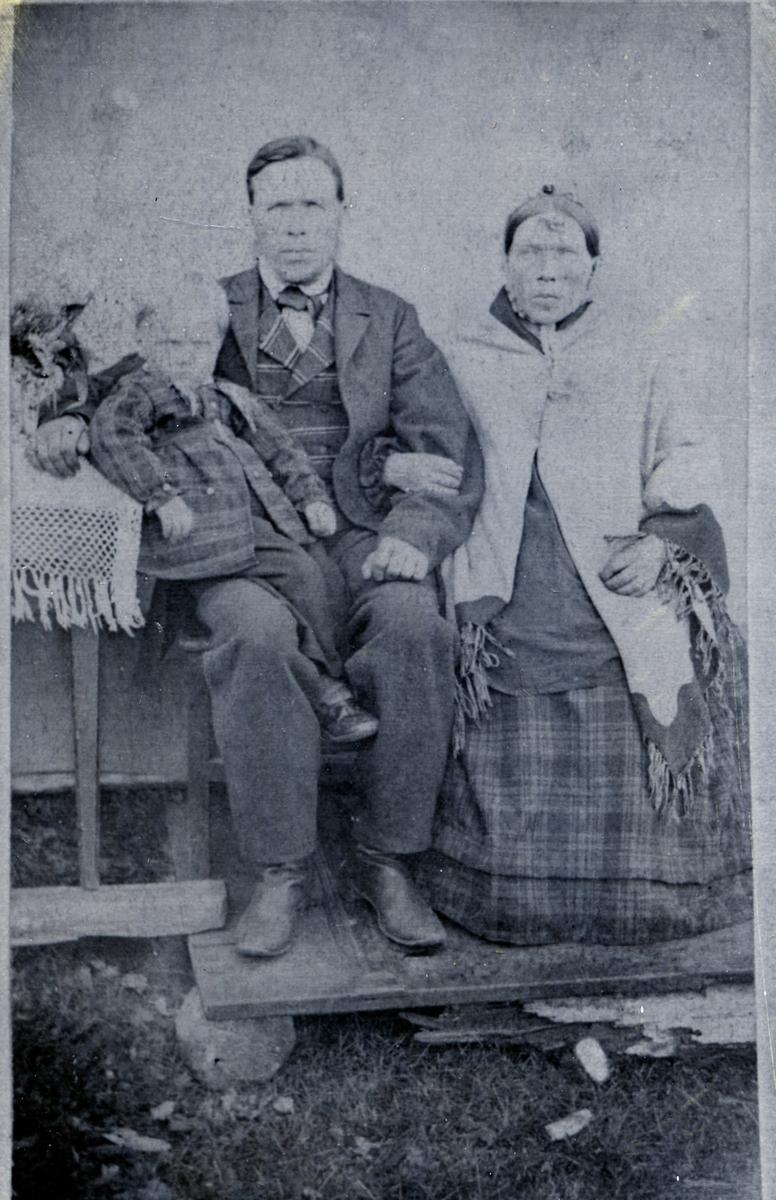 Kvinne og mann sittende foran lerret. Mannen har et barn på kneet. Bildet er tatt ute, de sitter på en oppbygd platting på grasmark. Barnet er John, som tok etternavnet Aspholt