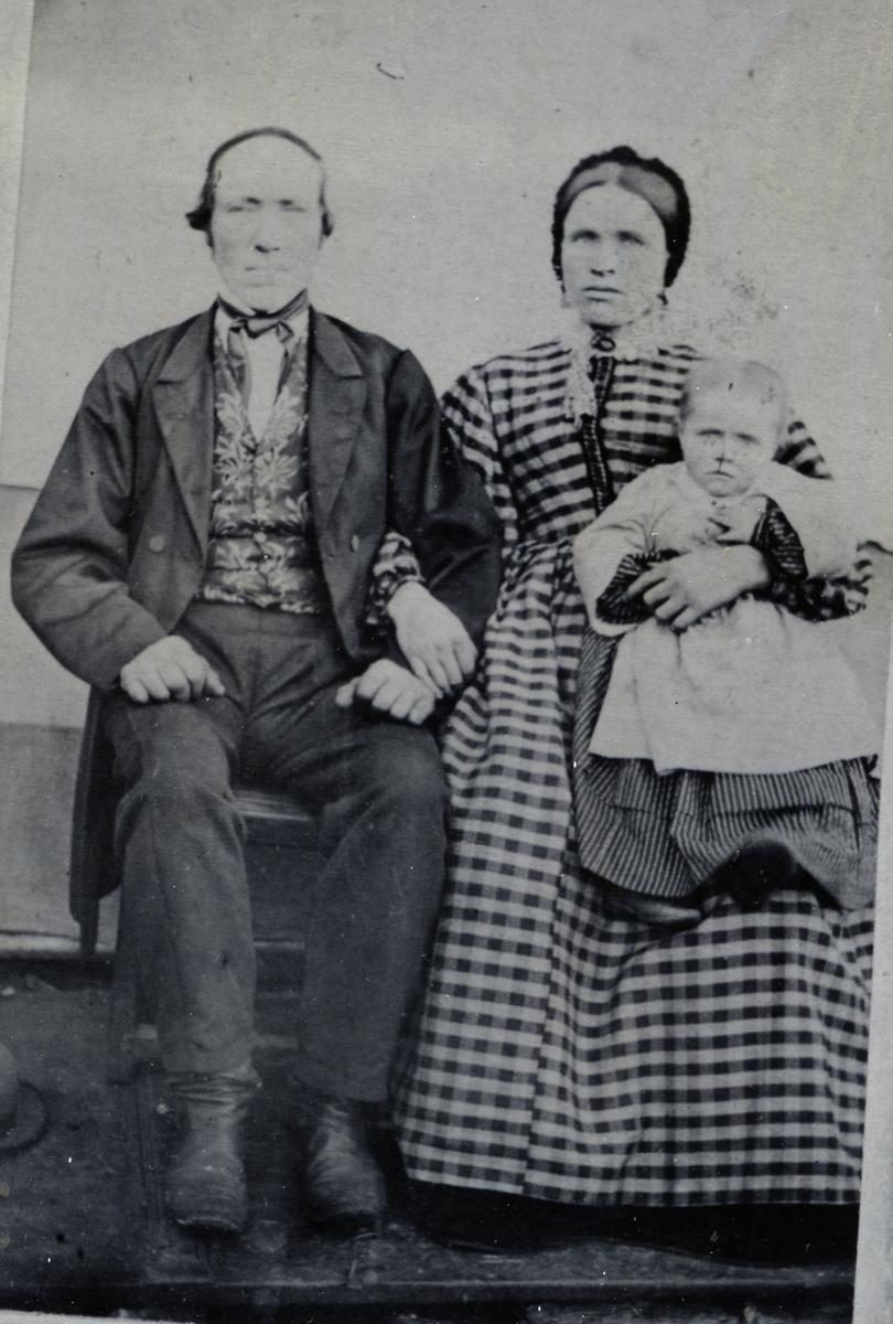 Kvinne og mann sittende foran lerret på oppbygd platting. Bildet er tatt ute på grasmark. Kvinna har datteren på fangen.