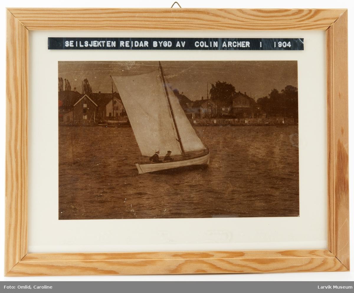 """Seilsjekten """"Reidar"""" bygget av Colin Archer i 1904. Tatt utenfor Skottebrygga på 1900-tallet. Ombord: Losoldermann Thommessen og sønnen Reidar"""