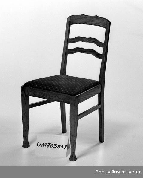 Ur lappkatalogen:  Stol. Trä. Fernissad. Sitsen klädd med vinrött tyg. Ryggstödets höjd: 44 cm, benens höjd: 43, sitsens mått: 35 x 43,5 x 41 cm.