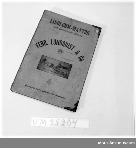 """Katalog. Text på framsidan: """"LINOLEUM-MATTOR med genomgående mönster. FERD. LUNDQUIST & Co. Kung. Hofleverant. FL & Co ETABL 1864 Profverna torde godhetsfullt returneras"""". Bild på två hästar som drar en vagn med två kuskar. På vagnen står det """"FERD: LUNDQUIST & Co."""". På första sidan står det:""""Grand Prix St. Louis 1904, Paris 1900, Staatpreis 1896, Görliz 1905, Rixdorfer Linoleum Patent-Inlaid. (Munster durch und durch) 200 cm breit Dessin J.102 Masstab naturliche Grösse. Dieses Papiermuster giebt nur das Dessin an, während die Beschaftenheit der Ware aus beifolgender Qualitätsprobe zu ersehen ist."""". Metallbeslag på hörnen. Exempel på s.k. genomgjutna korkmattor eller linoleummattor samt linoleumtapeter. Tillverkningsort förmodad utifrån nedanstående artikel och uppgift i katalogen. Pärmen låg kvar efter en loppmarknad i Strömstad som Röda Korset anordnat år 1992.  Bilagepärmen: """"Korkmattan på var mans golv"""", Sara Höglund, artikel i Byggnadskultur  3/07, s. 16-19."""