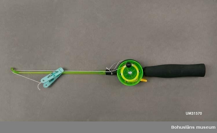 Krabbmeta för barn, märkt STOXDAL.  Svart handtag av skumplast med en rund plasttrissa med vitt lindat nylonsnöre, rulle. En klädnypa av turkos plast och en grön smal plastpinne att sätta framför rullen, är fästade ytterst på snöret. Snöret kan släppas ut genom att  trycka på en gul stoppknapp. Snöret lindas upp igen med ett vevhandtag som sitter på det gröna locket. Krabbmetan kallas krabbspö med klädnypa i företagets produktkatalog. Stoxdal AB är en sportfiskegrossist i Bohuslän   Inköpt till föremålssamlingarna i samband med utställningen Fri och ledig!? sommaren 2011. Text till utställningen Fri och Ledig!?: Sverige har fina möjligheter till fritidsfiske. 90 000 sjöar, 100 000 vattendrag och en lång kust. Det behöver inte vara dyrt. Men vi satsar gärna. Särskilt männen: 1,5 miljarder kronor läggs på båt och utrustning varje år. Fisketurism är en guldkantad nisch för näringslivet. Allt från hummersafari på Västkusten till exklusivt fiske i avlägsna fjällsjöar. Det finns en stor utländsk fisketurism. Utomlands är många vatten privatägda. Alla har rätt att fiska med handredskap vid kusten och i de fem stora sjöarna Vänern, Vättern, Mälaren, Hjälmaren och Storsjön. Man får meta, spinnfiska, pilka och pimpla och fiska med lina som har max 10 krokar. Till andra vatten kan man köpa fiskekort.