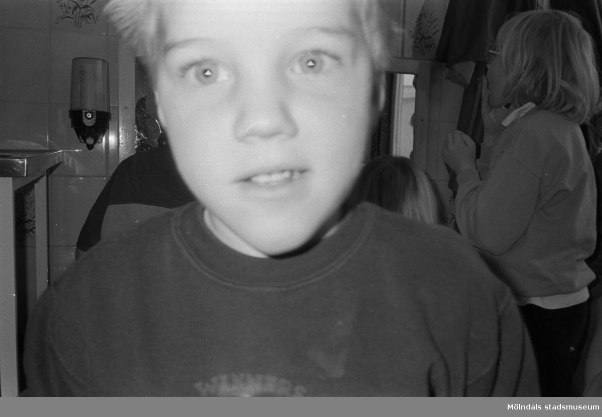 Ett barn, fotograferat i närbild, tittar rakt mot kameran. I bakgrunden syns flera barn. Bilden är ganska suddig. Katrinebergs daghem, 1992.