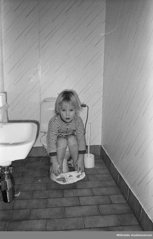 Ett barn som sitter på toaletten. På golvet ligger klinkers och till vänster syns ett handfat. Lille Skutt, Katrinebergs daghem, 1992.