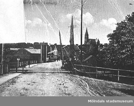 Avfotograferat vykort i dåligt skick av Mölndalsbro, cirka 1920. Kyrkan syns i bakgrunden.