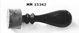 """Stämpel med svart droppformat handtag med två svarvade dekorringar. Stämpeldelen oval med stämpel: I mitten ett ankare omslingrat av ankartrossen. Ovanför detta en sluten, kunglig krona. Runt kanten texten: """"  H.M. Kryssare Göta lejon  """"."""