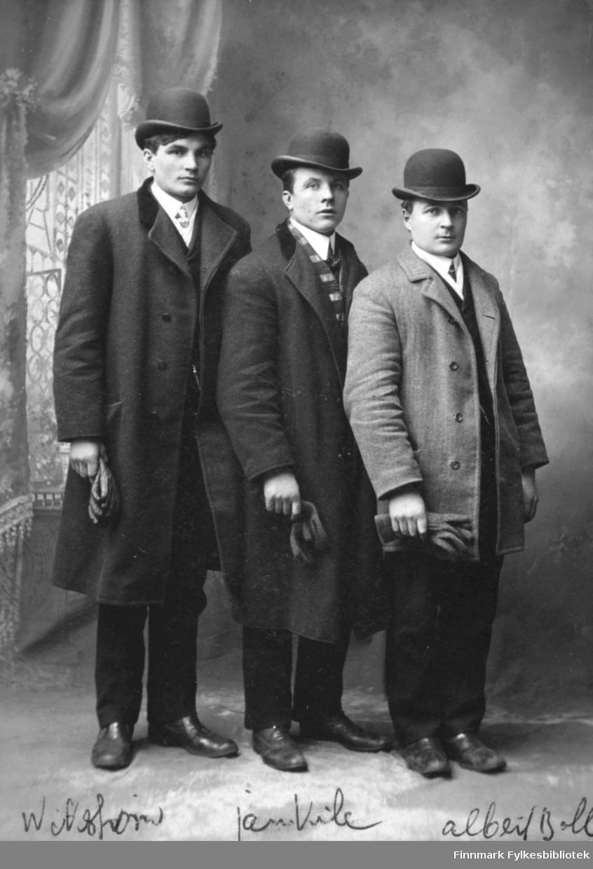 Portrett av tre unge mann. Herrene står i rad hos fotografen i Milwaukee, Usa. Alle er kledd i fine dresser med knaller og hansker. Den korteste av herrene (han til høyre) er Albert Emanuel Palo fra Vadsø som emigrerte til Michgian, Usa, i begynnelsen av 1900-tallet.