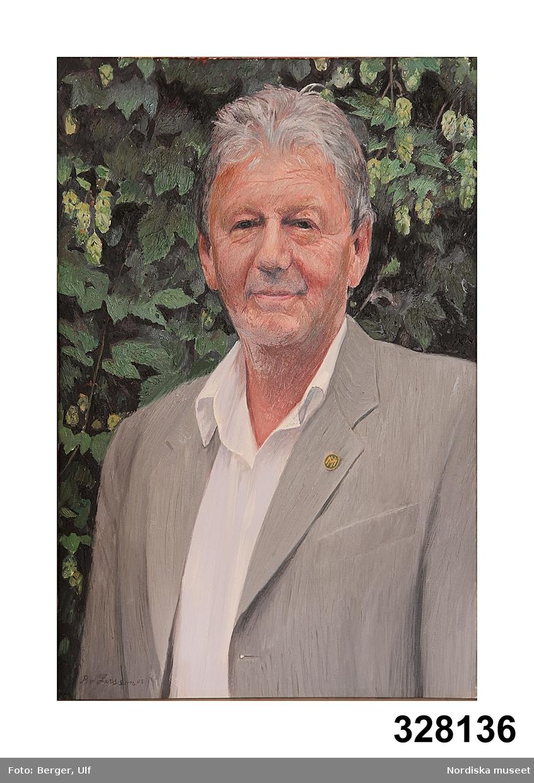 Porträtt föreställande Lars Löfgren klädd i grå kavaj och vit skjorta uppknäppt i halsen. I knapphålet sitter Nordiska museets märke med NM. Bakgrund av ymnig grön humle. /2003-11-19 Sigrid Eklund