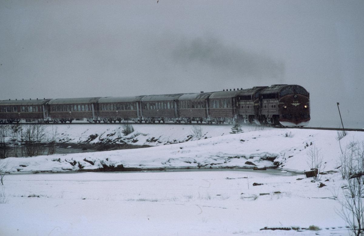 Nordgående dagtog 451 Trondheim - Bodø kjører ut fra Mo i Rana i snøvær. NSB dieselelektriske lokomotiver type Di 3.