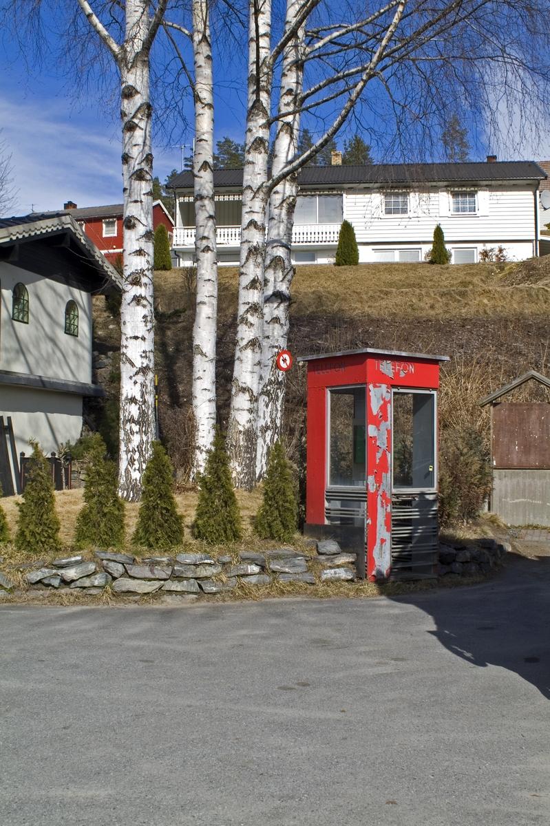 Denne telefonkiosken står på Krøderen torg i Krødsherad, og er en av de 100 verna telefonkioskene rundt om i Norge. De røde telefonkioskene ble laget av hovedverkstedet til Telenor (Telegrafverket, Televerket) Målene er så å si uforandret.  Vi har dessverre ikke hatt kapasitet til å gjøre grundige mål av hver enkelt kiosk som er vernet.  Blant annet er vekten og høyden på døra endret fra tegningene til hovedverkstedet fra 1933. Målene fra 1933 var: Høyde 2500 mm + sokkel på ca 70 mm Grunnflate 1000x1000 mm. Vekt 850 kg. Mange av oss har minner knyttet til den lille røde bygningen. Historien om telefonkiosken er på mange måter historien om oss.  Derfor ble 100 av de røde telefonkioskene rundt om i landet vernet i 1997. Dette er en av dem.