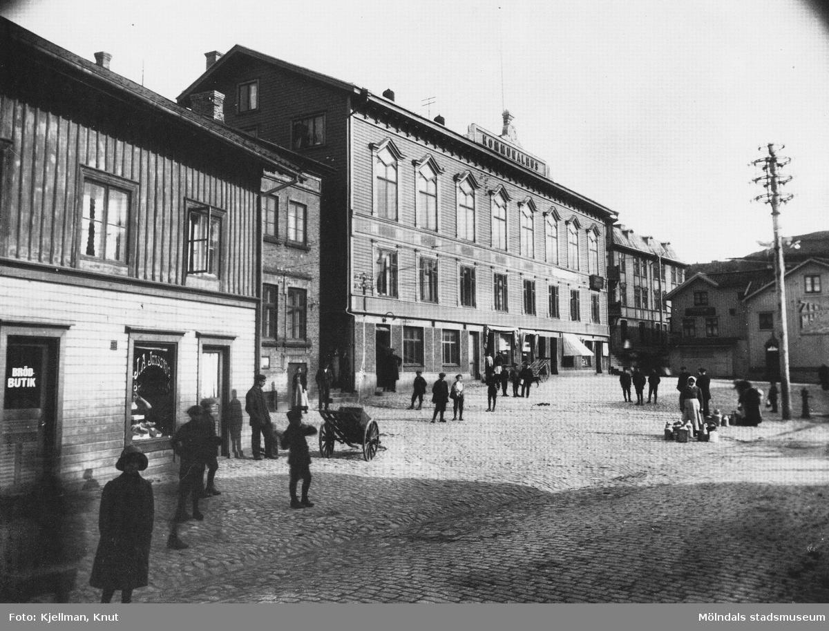 Det stenlagda gamla torget med kärror, folk och kommunalhuset som fasad. J.A. Jonssons brödbutik i förgrunden. Antagligen innan år 1919.