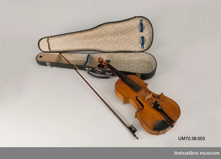 Ur lappkatalogen: Fiol. Längd: 59 cm. Br. 20 resp. 16. cm. Höjd: 4: cm. 3 strängar varav 1 lös. Tillverkare Albin Andersson 1929. Vänersborg. 4 st. reservsträngar i påsar varav en sensträng (UM70.38.003 d - g), låda till fiolen UM70.38.003 b. En stråke med sträng lös.  Inuti resonanslådan finns en papperslapp fastklistrad med följande information:  Albin Andersson Vänersborg 1929 N:2