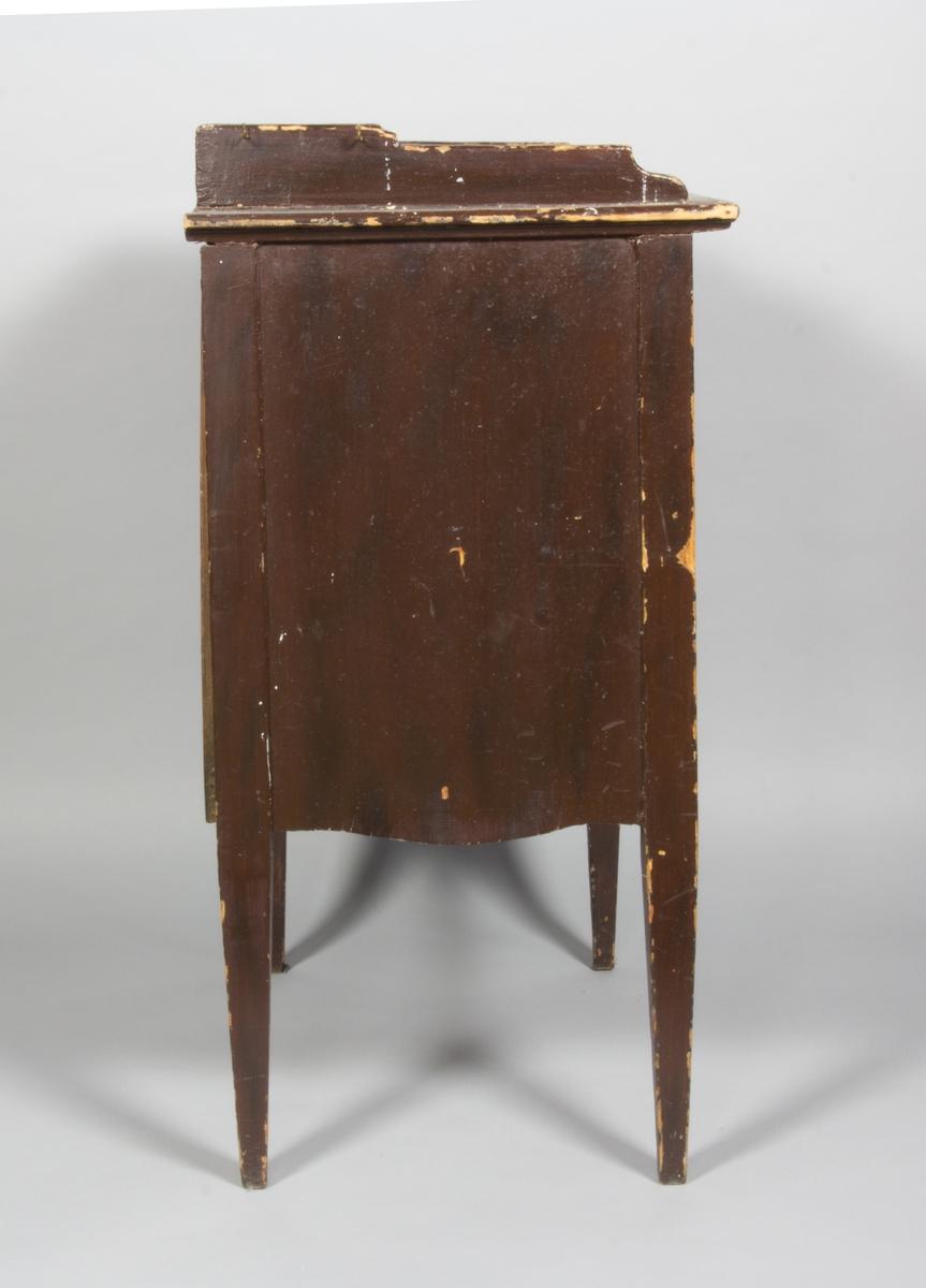 Kommod på höga ben, brunmålad. Lister på tre av skivans sidor. Två dörrar och en låda. Två metallkrokar på sidan för att hänga handduk.